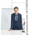 Portrait of smiling business woman near flipchart 16729943