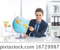 Smiling business woman pointing on earth globe 16729987