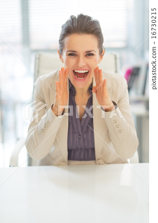 Happy business woman shouting through megaphone shaped hands 16730215