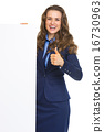 Happy business woman showing blank billboard and thumbs up 16730963