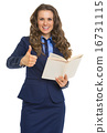 Happy business woman with book showing thumbs up 16731115