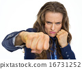 Serious business woman punching in camera 16731252
