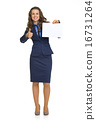 Full length portrait of happy business woman showing blank paper 16731264