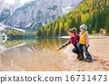 Mother pointing and kneeling next to daughter at Lake Bries 16731473
