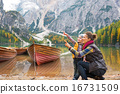 Happy mother and baby pointing on copy space while on lake braie 16731509