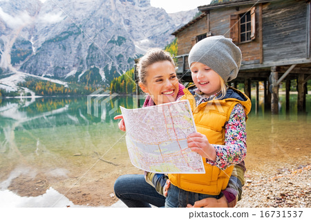 Portrait of happy mother and baby with map on lake braies in sou 16731537
