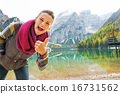 Happy young woman on lake braies in south tyrol, italy showing t 16731562