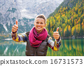 Happy young woman on lake braies in south tyrol, italy showing t 16731573
