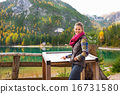 Young woman pointing in information board while on lake braies i 16731580