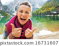 Portrait of happy young woman on lake braies in south tyrol, ita 16731607