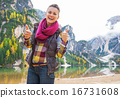 Portrait of smiling young woman on lake braies showing thumbs up 16731608