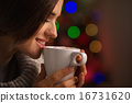 Happy young woman enjoying cup of hot beverage in front of Chris 16731620