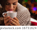 Young woman holding cup of hot chocolate with marshmallows 16731624