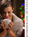 Happy woman holding cup of hot chocolate with marshmallows 16731631