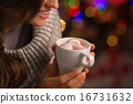 Closeup on hot chocolate with marshmallows in hand of happy woma 16731632