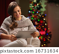 Happy woman sitting with tablet PC in front of Christmas tree 16731634