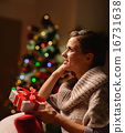 Dreaming young woman sitting chair with Christmas present box 16731638