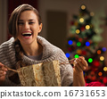 Happy woman with shopping bag in front of Christmas tree 16731653