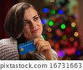 Portrait of thoughtful woman with credit card in front of Christ 16731663
