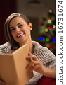 Happy woman in front of Christmas tree reading book 16731674