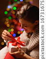 Happy young woman sitting chair and opening Christmas present bo 16731675