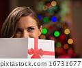 Girl hiding behind Christmas postcard 16731677