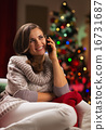 Young woman speaking mobile phone in front of Christmas tree 16731687