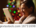 Smiling young woman using tablet pc in front of christmas tree 16731698