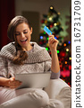 Happy woman in front of Christmas tree making online purchases 16731709