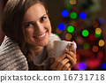 Happy young woman enjoying cup of hot chocolate in front of Chri 16731718