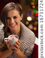 Smiling woman holding cup of hot chocolate with marshmallows 16731724