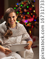 Happy young woman near christmas tree using tablet pc 16731733