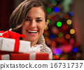 Happy young woman holding Christmas gift boxes 16731737