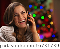 Smiling young woman speaking mobile phone in front of Christmas 16731739