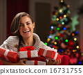 Happy young woman holding Christmas present boxes 16731755