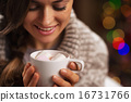 Happy young woman holding cup of hot chocolate with marshmallow 16731766