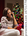 Young woman talking cell phone near christmas tree 16731770