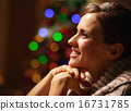 Portrait of happy young woman in front of christmas lights 16731785