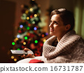 Happy young woman watching tv in front of christmas tree 16731787