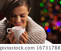 Happy woman with cup of hot chocolate with marshmallow in front 16731788