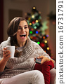 Surprised young woman with cup of hot chocolate watching tv 16731791