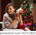 Happy young woman shaking present box near christmas tree 16731802