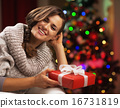 Portrait of smiling young woman near christmas tree with present 16731819