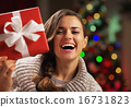 Happy young woman looking out from present box in front of chris 16731823