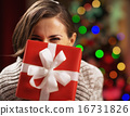 Happy young woman holding christmas present box in front of face 16731826