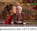 Portrait of mother and baby in christmas decorated kitchen 16731835