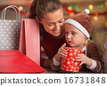 Happy mother and baby among christmas shopping bags 16731848