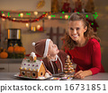 Smiling mother and baby with christmas cookie house in kitchen 16731851