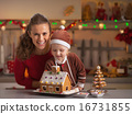 Smiling mother and baby decorating christmas cookie house in kit 16731855