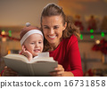 Happy mother and baby reading book in christmas decorated kitche 16731858
